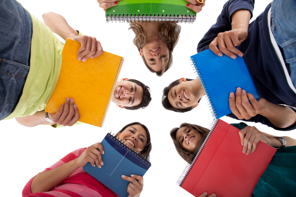 Group of students in a circle holding notebooks - isolated over white